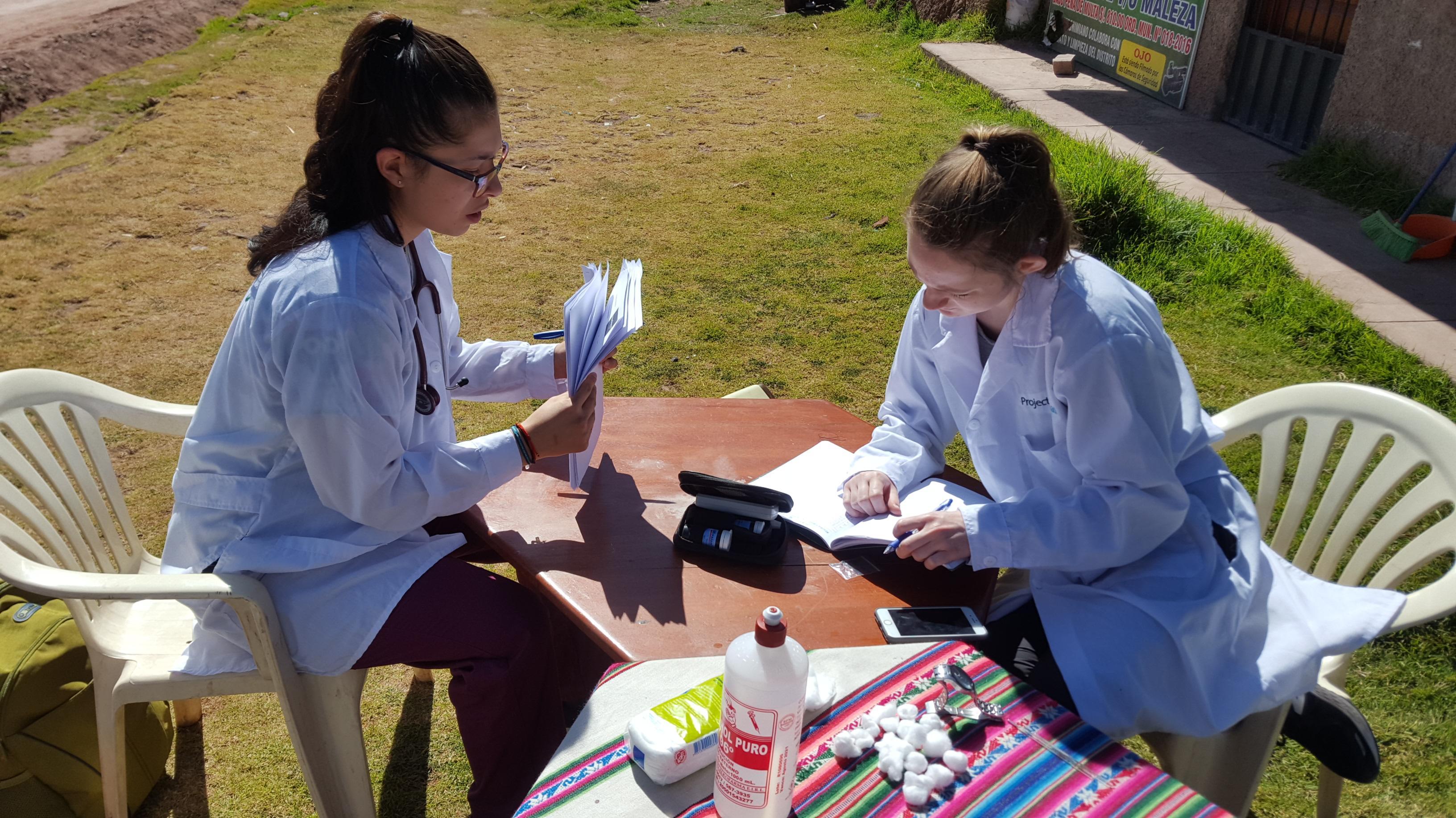 Par de estudiantes en una pasantía de nutrición revisando información de pacientes durante una brigada en Perú.